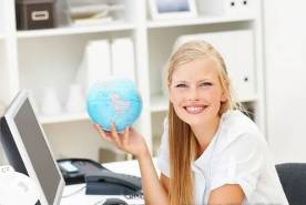 A girl at the computer holds a globe in her yand.