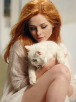 Redhead girl with a cat in the bed