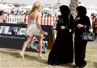 Sexy girl in short dress on the high heels and two Muslim women in long black dresses.