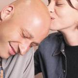 woman kisses bald-headed man.