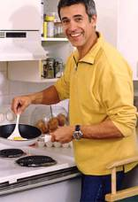 An energetic young man in the kitchen frying eggs
