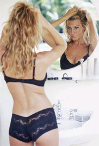 slim girl in a black underwear in front of a mirror