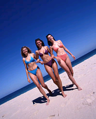 Three young girls in bathing suits are on the beach